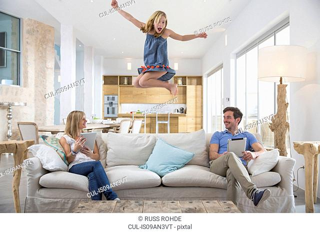 Girl jumping mid air from living room sofa whilst parents use digital tablet