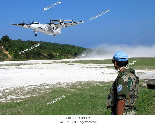 Soldier of the 'United Nations Stabilisation Mission in Haiti' secures UN aircraft with machine gun which takes off from the unpaved runway, Haiti, Grande Anse