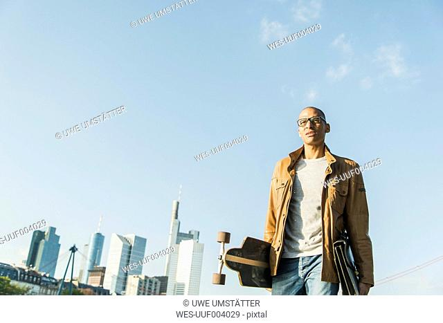 Germany, Frankfurt, man on the go carrying skatebaord and briefcase