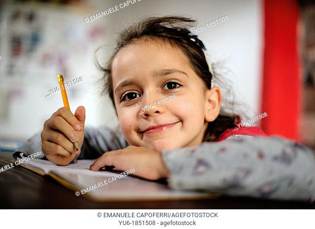 Child smiles while exercise the tasks of school