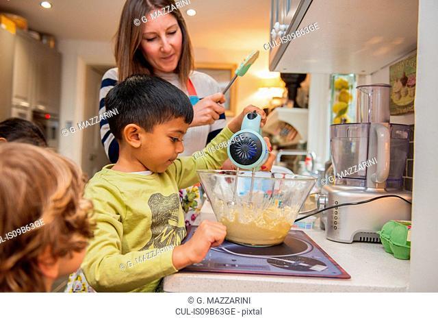 Childminder and children baking