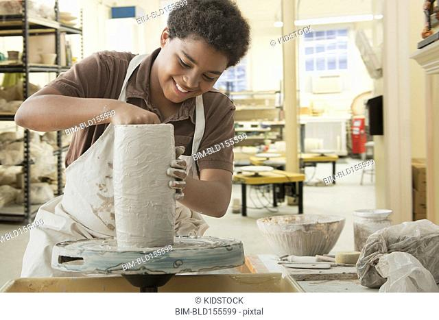 Boy forming pottery on wheel in studio