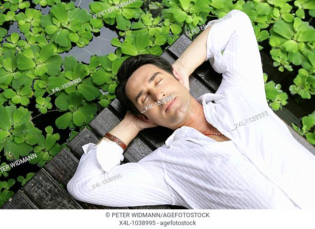 Man enjoying holidays at tropical garden in Thailand