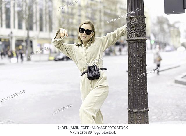 fashionable woman at lamp post at street during fashion week, in Paris, France
