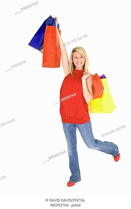 Beautiful Caucasian teen holding shopping bags while standing on a white background