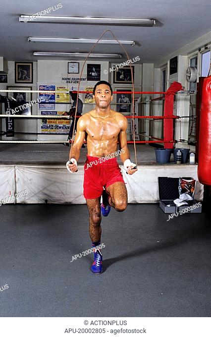 Boxer working out with a skipping rope in a gym