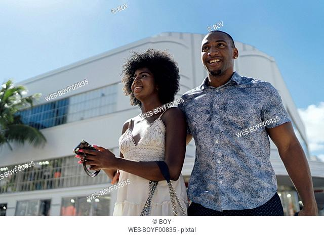 USA, Florida, Miami Beach, happy young couple on the move in the city