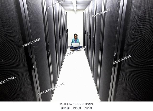 Black businesswoman typing on laptop in office technology room