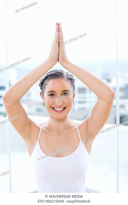 Cheerful sporty brunette sitting in yoga posture