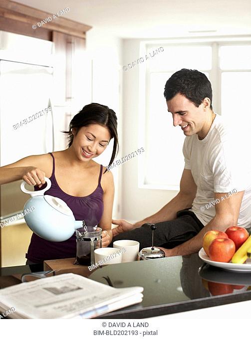 Couple preparing coffee in kitchen