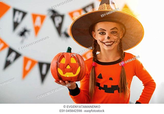 happy laughing child girl in pumpkin costume to halloween