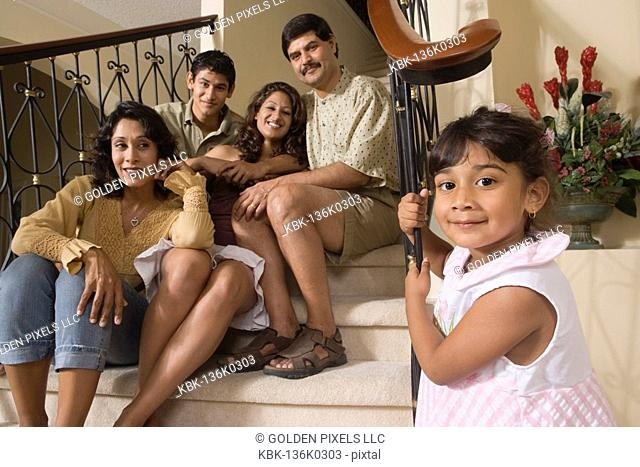 Portrait of little Indian girl and her family sitting together on stairs