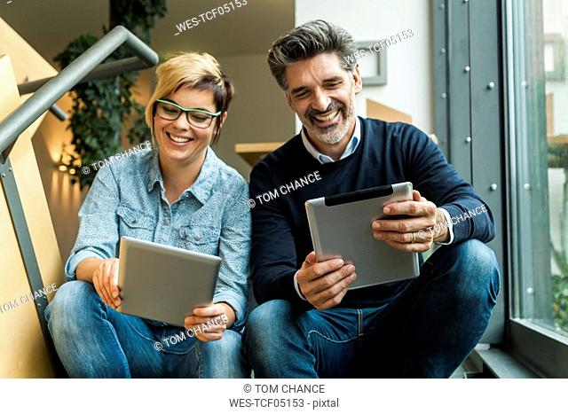 Businesman and woman sitting on stairs, using digital tablets