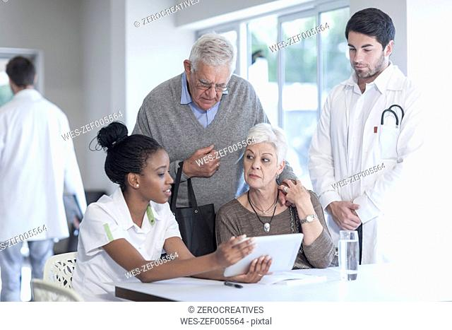 Senior couple at clinic talking to doctor and nurse