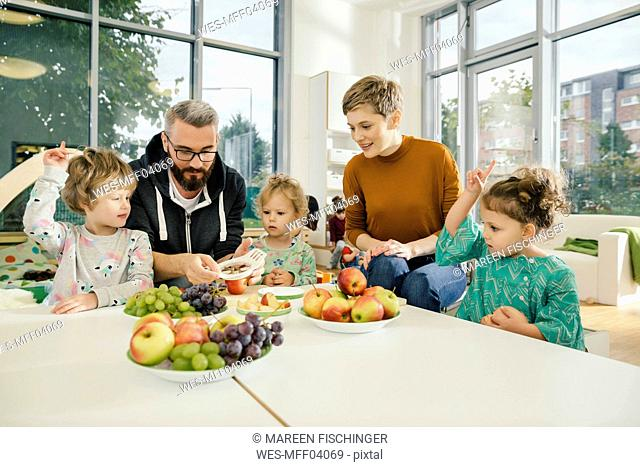 Children and teachers preparing fruit in kindergarten