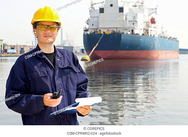 Close up portrait of a docker in front of a large oil tanker, moored off in an industrial harbor