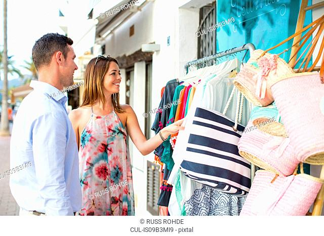 Couple shopping for beach bag at shop front, Majorca, Spain