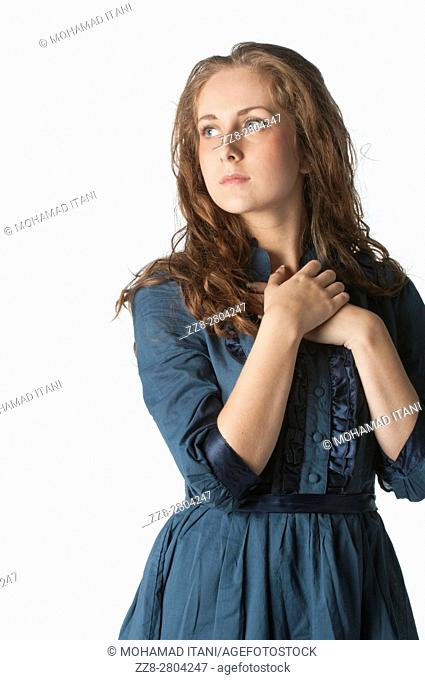 Young woman hands over heart looking away against a white background
