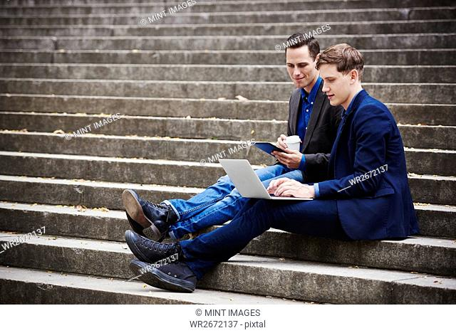 Two young men sitting on a flight of steps looking at a laptop together