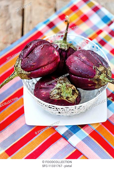 Fresh aubergines in a bowl on a wooden table