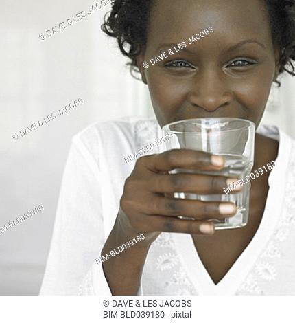 African woman drinking glass of water