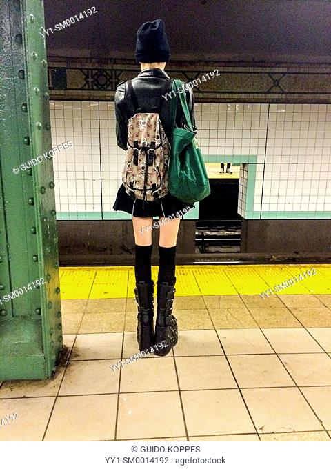 Subway, New York, USA. Young, attractive, caucasian and very slender girl waiting on a subway station platform for the next train home