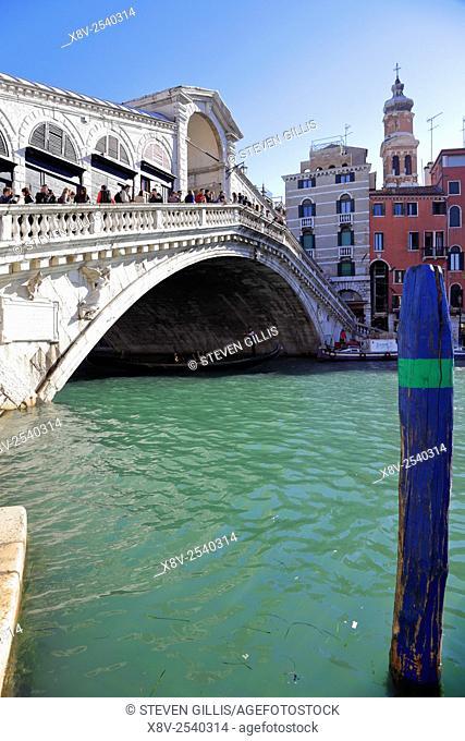 Gondola passes under the Rialto Bridge on the Grand Canal, Venice, Italy