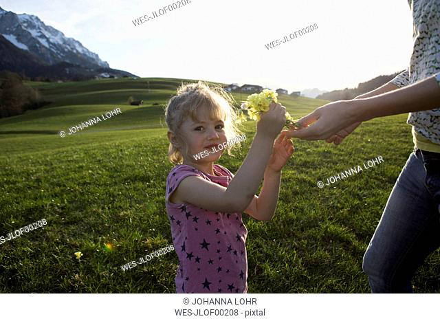 Austria, Tyrol, Walchsee, portrait of girl with mother holding flowers on an alpine meadow