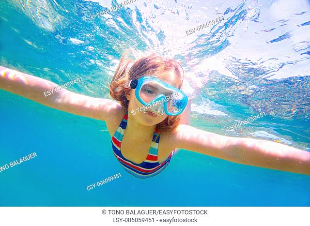 snorkeling blond kid girl underwater with goggles and swimsuit in Mediterranean sea