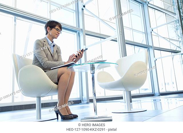 Businesswoman with cell phone in modern lobby