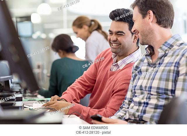Men laughing at computer in adult education classroom