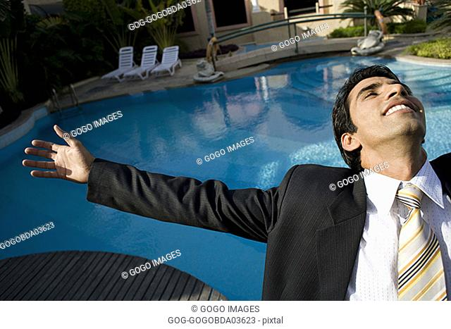 Businessman standing by swimming pool with arms outstretched