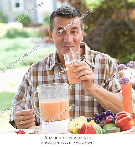 Mature man drinking juice with a drinking straw