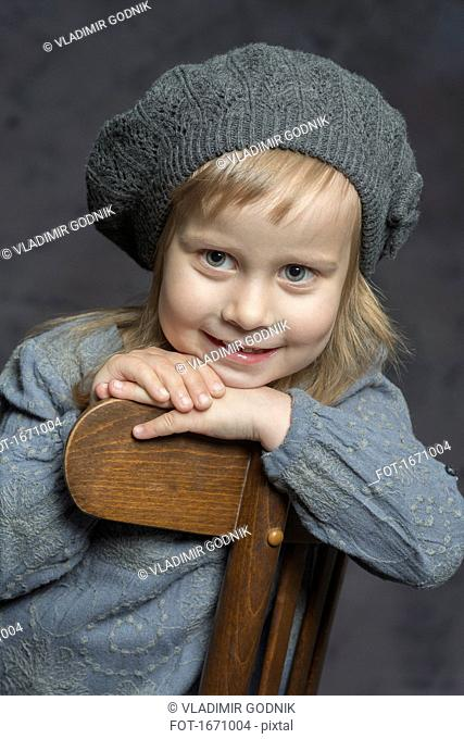 Cute smiling girl wearing knit hat sitting on wooden chair against gray background