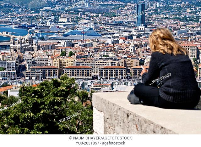 A tourist woman sees a panorama of the old Marseille, France