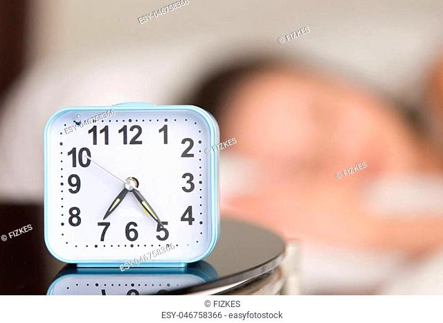 Close up image of modern alarm clock on bedside table with blurred person sleeping in bed in background. Wake up in early morning, stable sleep routine