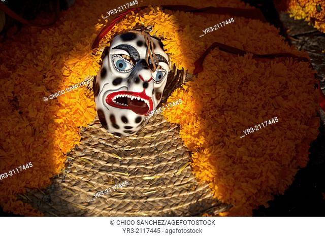 A black mask and a hat decorated with marigold flowers are ready to be used to dance the Danza de los Tlacoleros, by a group from Zumpango, Estado Guerrero