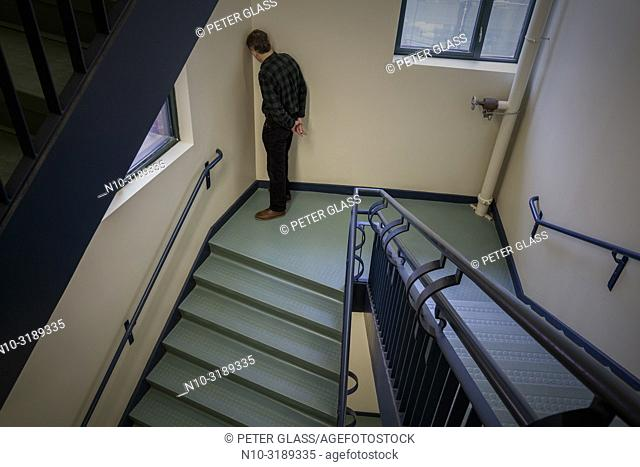 Man leaning against a wall at the bottom of a stairway