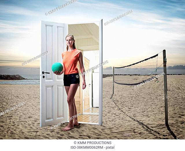 Woman emerging from door on beach