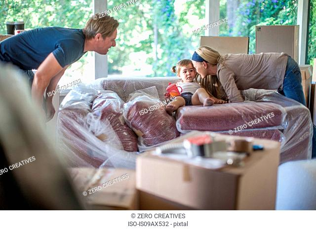 Moving house: young girl sitting on bubble wrapped sofa