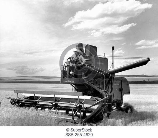 Farmer using a combine harvester in a field, Montana, USA