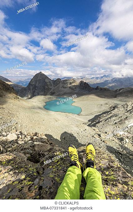 Hiker lies on rocks around Lej Lagrev, Silvaplana, canton of Graubünden, Engadine, Switzerland