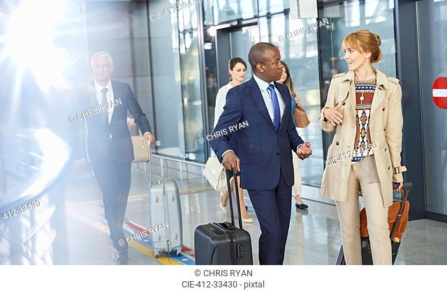 Business people talking and walking with suitcases in airport concourse