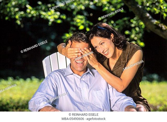 Laughing couple in the garden, woman keep shutting the eyes of the man