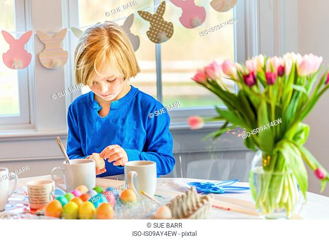 Boy at table decorating eggs for Easter