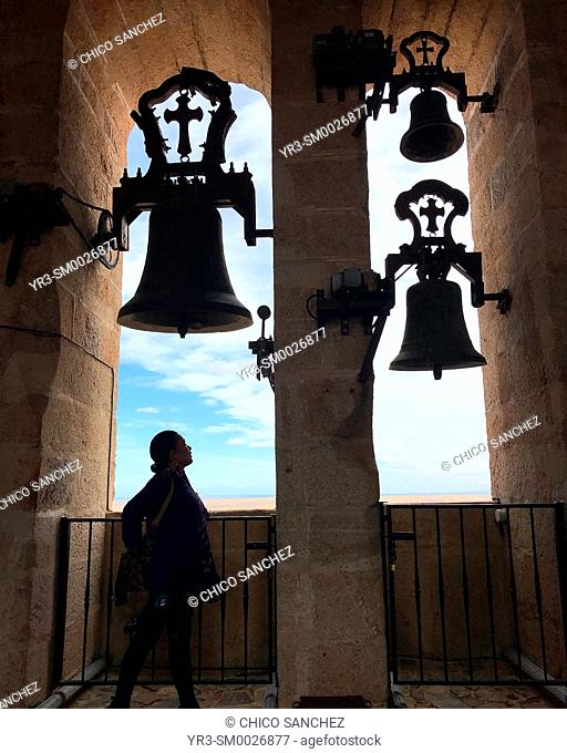 A woman stands near the bells of the bell tower of the Church Con-cathedral of Santa María ( Concatedral de Santa Maria ) of Caceres, Extremadura, Spain