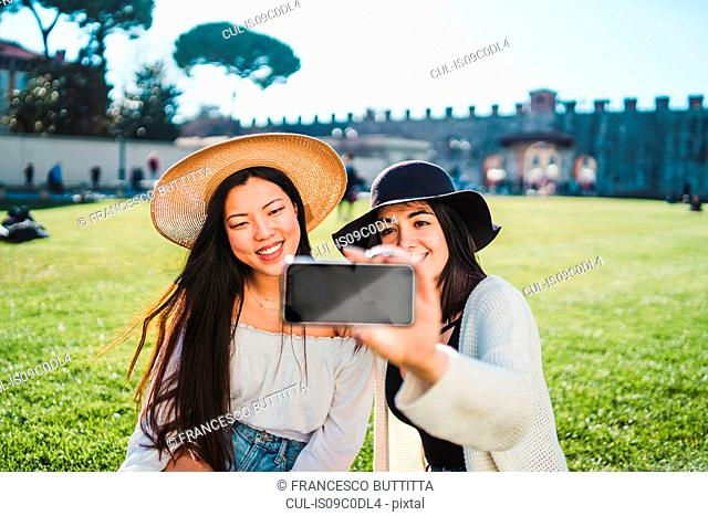 Friends taking selfie on field, Pisa, Toscana, Italy