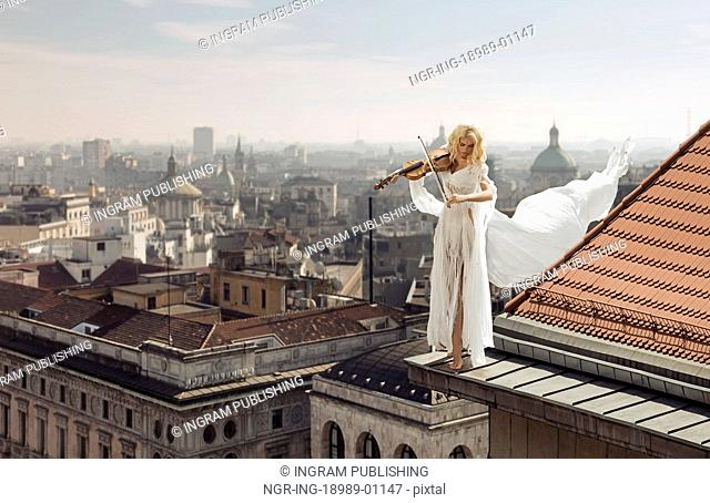 Lady playing the violin on the top of the edge of the roof