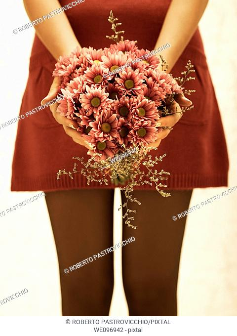Good-looking young woman in a red dress holding a flower bouquet