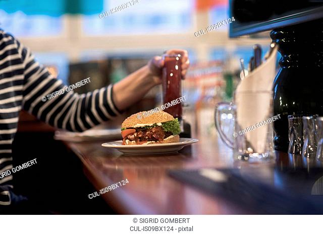 Woman with plate of burger on pub counter top